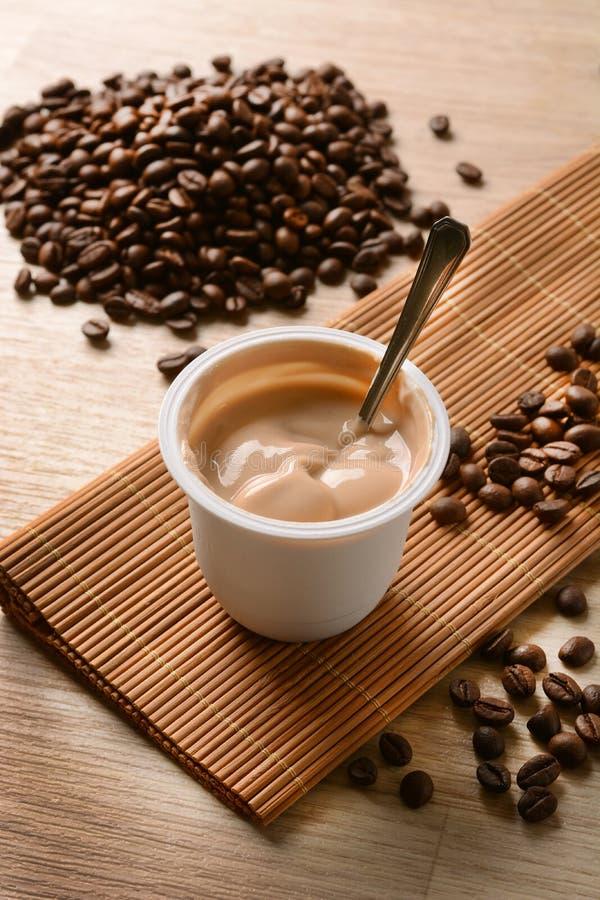 yaourt Café-assaisonné avec des grains de café autour photographie stock libre de droits
