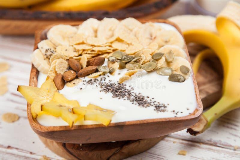 Yaourt de banane avec des graines et des cornflakes photo stock