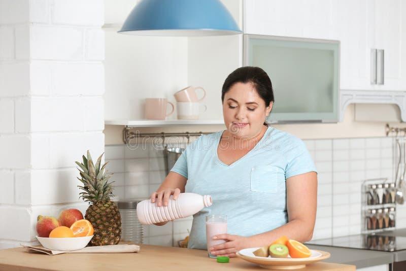 Yaourt de versement de femme de bouteille dans le verre dans la cuisine photos stock