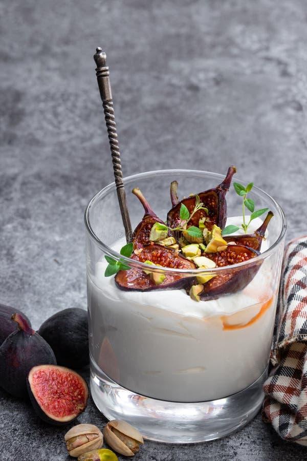 Yaourt fait maison avec les figues et la pistache grillées sur la table grise image libre de droits