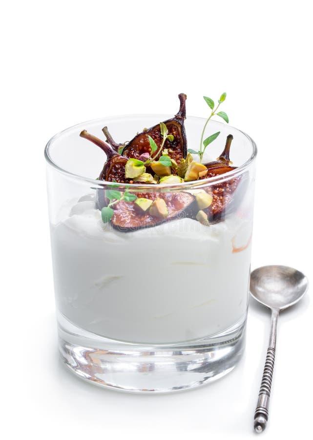 Yaourt fait maison avec les figues grillées et la pistache d'isolement sur le blanc photographie stock libre de droits