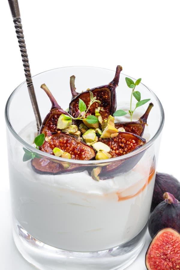 Yaourt fait maison avec les figues grill?es et la pistache d'isolement sur le blanc photos stock