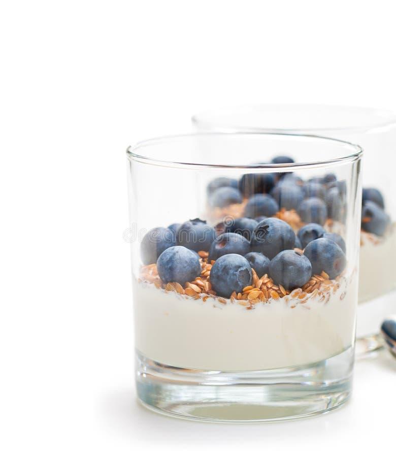 Yaourt frais dans un verre avec le lin et les myrtilles entiers sur le petit morceau image libre de droits