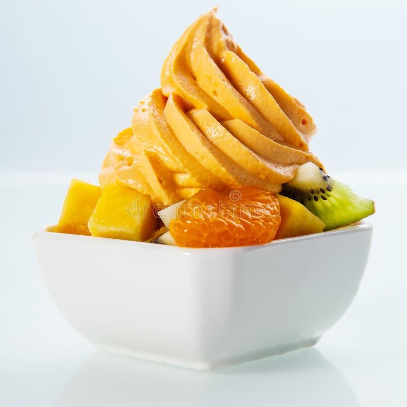 Yaourt jaune congelé gastronome sur des fruits frais images stock