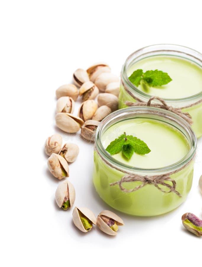 Yaourt naturel de pistache dans un petit pot en verre d'isolement sur le blanc images stock