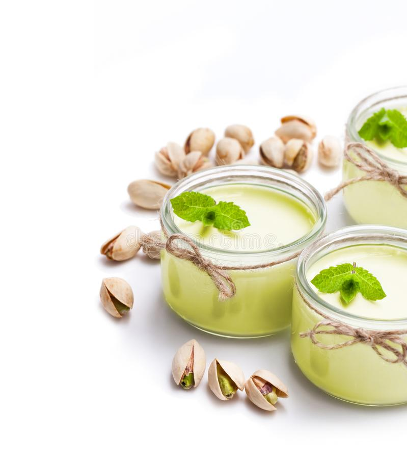 Yaourt naturel de pistache dans un petit pot en verre d'isolement sur le blanc photo stock