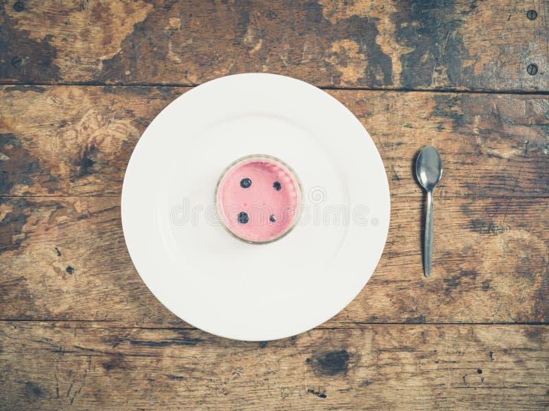 Yaourt rose d'un plat avec la cuillère photographie stock libre de droits