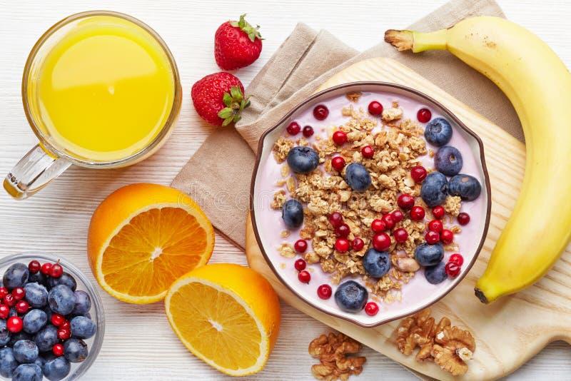 Yaourt sain de petit déjeuner avec la granola et les baies images libres de droits