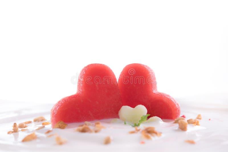 Yaourt simple avec la pastèque fraîche de forme de coeur sur le dessus dans la cuvette d'isolement sur le fond blanc photos libres de droits