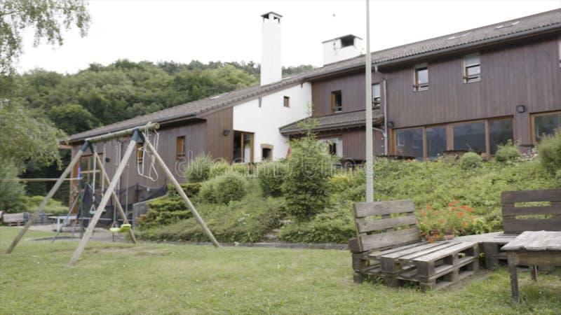 Yard admirablement conçu près de la maison en bois moderne par temps pluvieux action Arrière-cour avec les bancs faits main et photographie stock