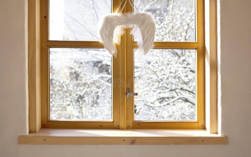 Yard d'hiver vu la fenêtre avec la décoration de Noël d'ailes d'ange image stock