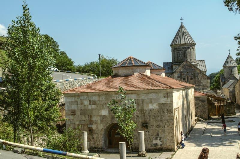 Yarda del monasterio Haghartsin que pasa por alto el refectorio con dos bóvedas, la iglesia de la Virgen María bendecida y la igl fotografía de archivo