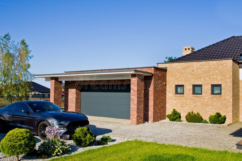 Yarda moderna de la casa con el garaje y el coche costoso foto de archivo