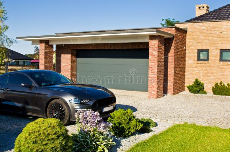 Yarda moderna de la casa con el garaje y el coche costoso imagen de archivo