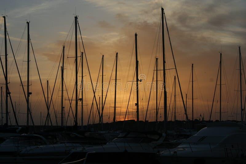 Yardas de barcos en la puesta del sol imagenes de archivo