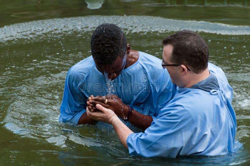 Yardenit, Israël - 29 Decembre 2012 : un homme prie après son baptême dans Jordan River Le prêtre tient ses mains images libres de droits