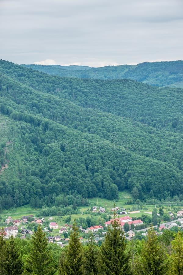 Resort city Yaremche in the valley of mountains. Yaremche resort city in the valley of Carpathian Mountains. Warm summer day, green wooded hills landscape royalty free stock photography
