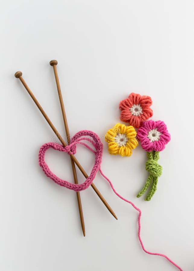 Yarn Crafts. Knitted pink heart and crochet flowers stock photos