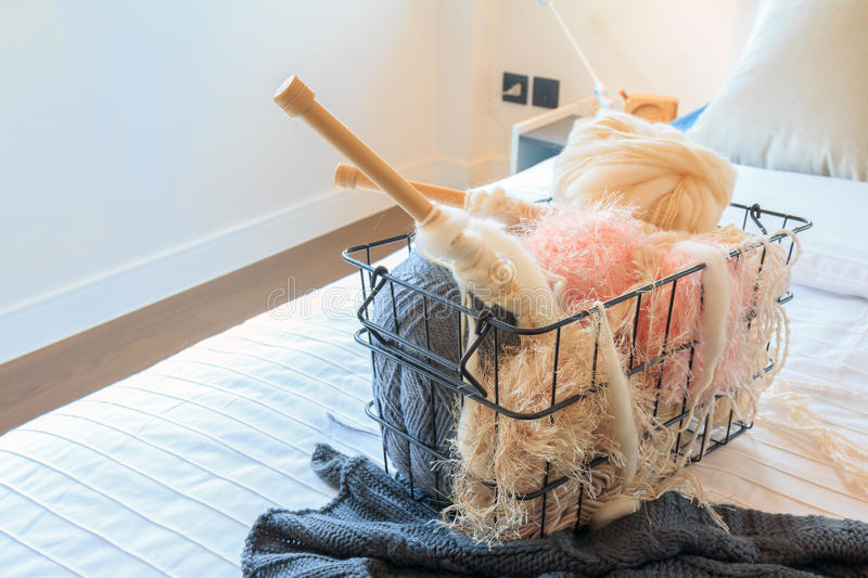 Yarn and crochet needles in a steel basket on a bed. Yarn and crochet needles in a steel basket on a bed in bedroom royalty free stock photo