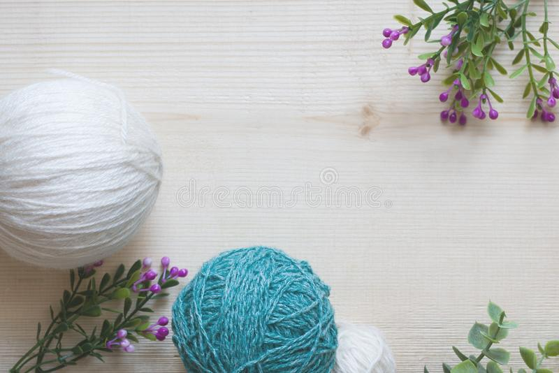 Yarn for knitting. Balls of yarn and flowers on a wooden background. Yarn for needlework. Flat lay, copy space, top view stock photos