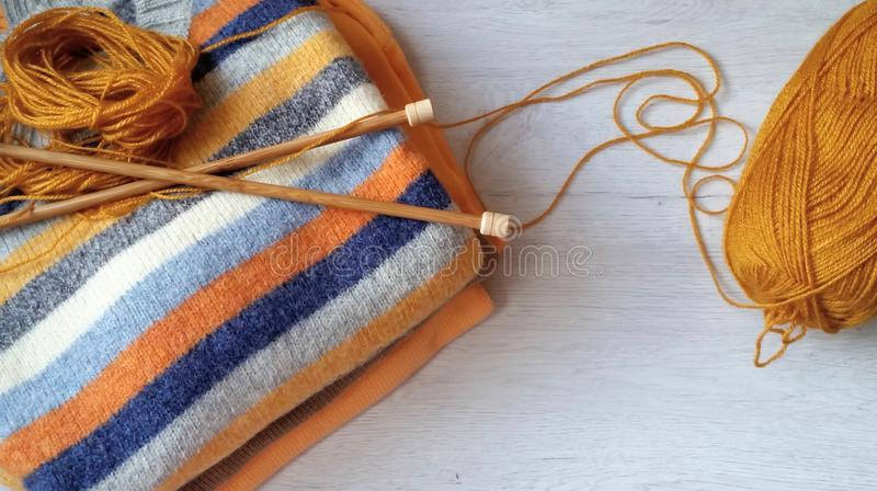 Yarn for knitting and handmade sweaters. In grey, orange, ocher and terracotta colors stock photo