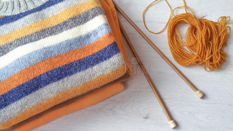 Yarn for knitting and handmade sweaters. In grey, orange, ocher and terracotta colors stock images