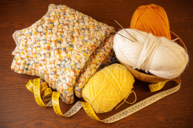 Yarn with knitting needles,knitted thing and measuring tape. Skeins of yarn with knitting needles,knitted thing and measuring tape on wooden background stock images