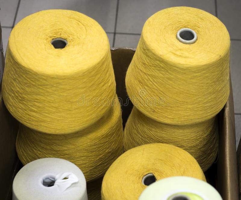 Yarn in mustard-colored bobbins in a box at the factory.  stock image