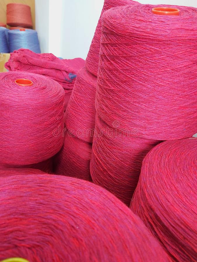 Yarn in red bobbins in a box at the factory.  royalty free stock images