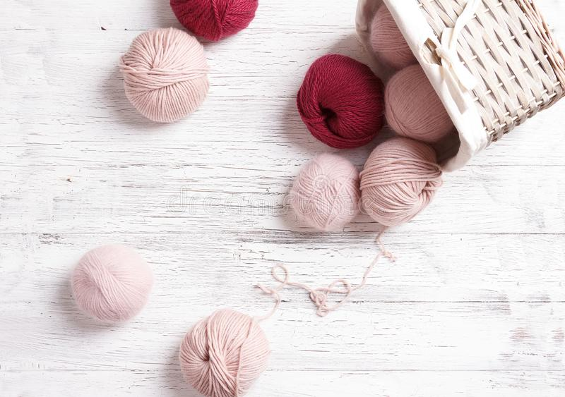 Yarn in wicker basket on white wooden background. royalty free stock images