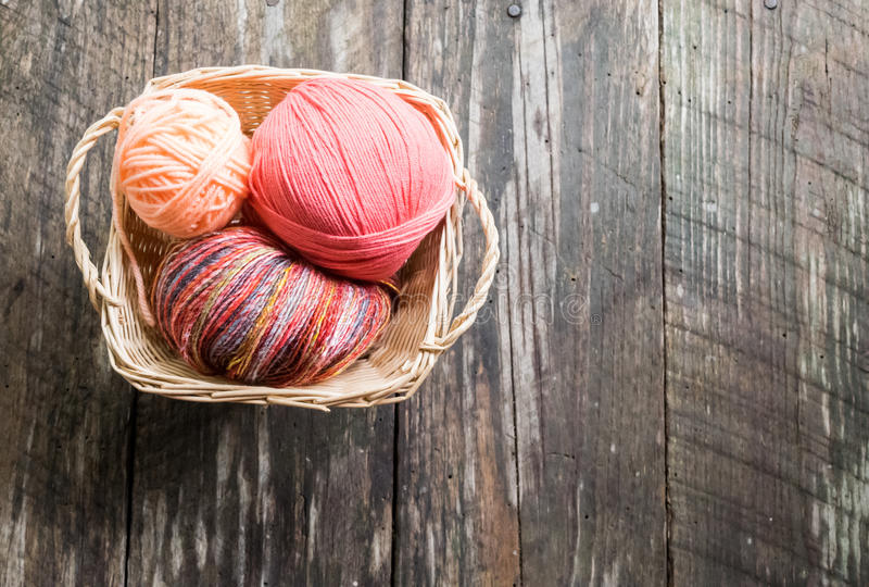 Yarn in worven basket; old wood planks background stock images