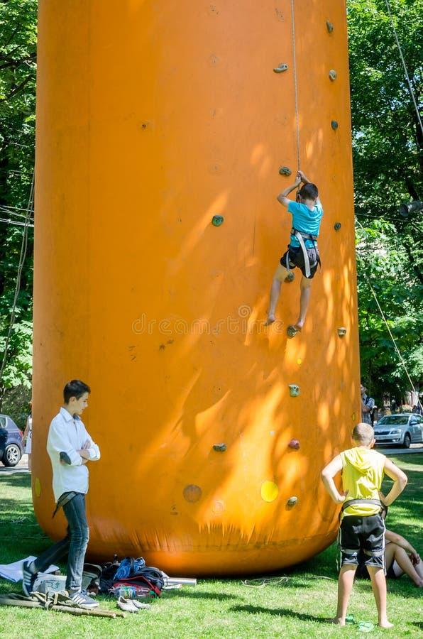 Yarych gataFest 2015 Barn konkurrerar i klättring på en uppblåsbar kulle som klättrar till överkanten royaltyfria foton