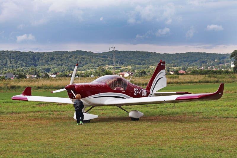 Yaslo,波兰- 2018年7月3日:小男孩在机场是对一架容易的两位子tuppovintovim飞机感兴趣 培养fut 库存照片