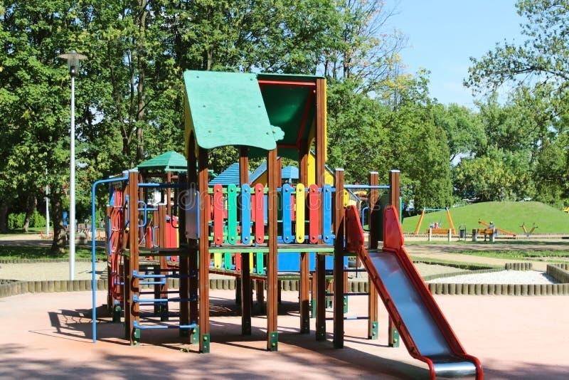 Yaslo, Польша - 12-ое июля 2018: Спортивная площадка ` s детей в парке между растительностью Пестротканые качания и здания для де стоковое изображение rf