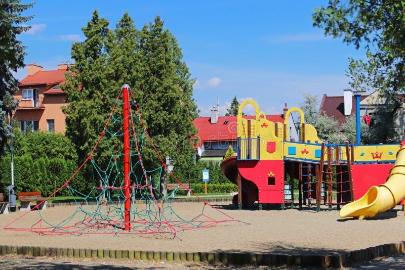 Yaslo, Польша - 12-ое июля 2018: Спортивная площадка ` s детей в парке между растительностью Пестротканые качания и здания для де стоковая фотография