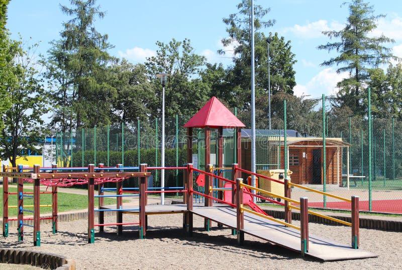 Yaslo, Польша - 12-ое июля 2018: Спортивная площадка ` s детей в парке между растительностью Пестротканые качания и здания для де стоковое фото rf