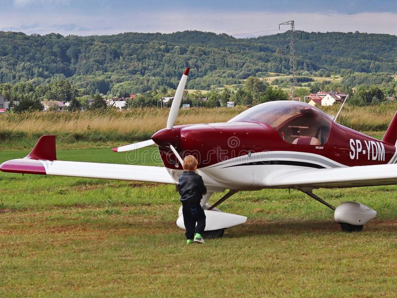 Yaslo, Poland - july 3 2018: The little boy at the airport is interested in an easy two-seat tuppovintovim airplane. Raising a fut stock image