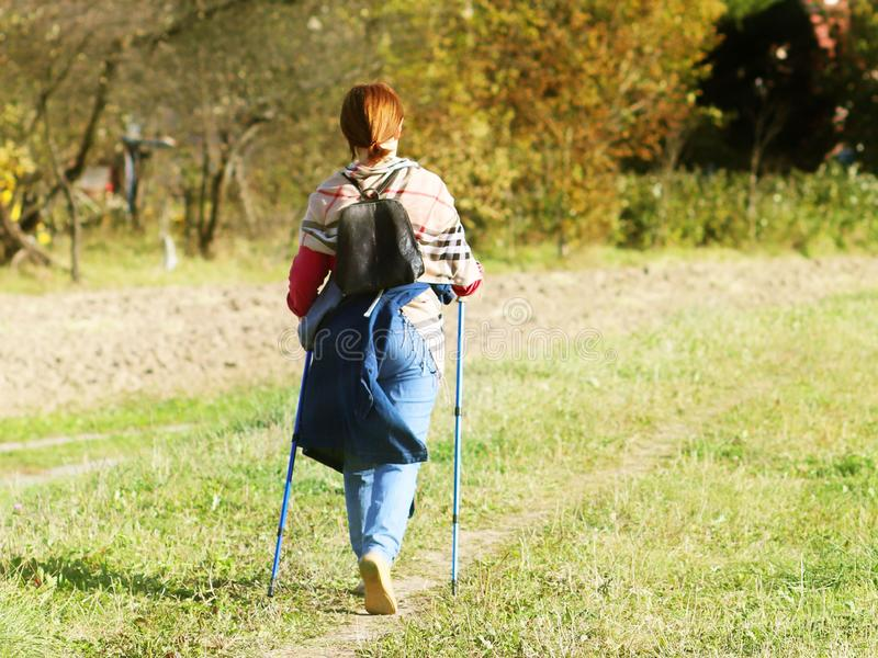 Yaslo, Poland - july 9 2018: Scandinavian / nordic walking. A woman in city clothes stroll through the summer`s grass in the rays royalty free stock photos
