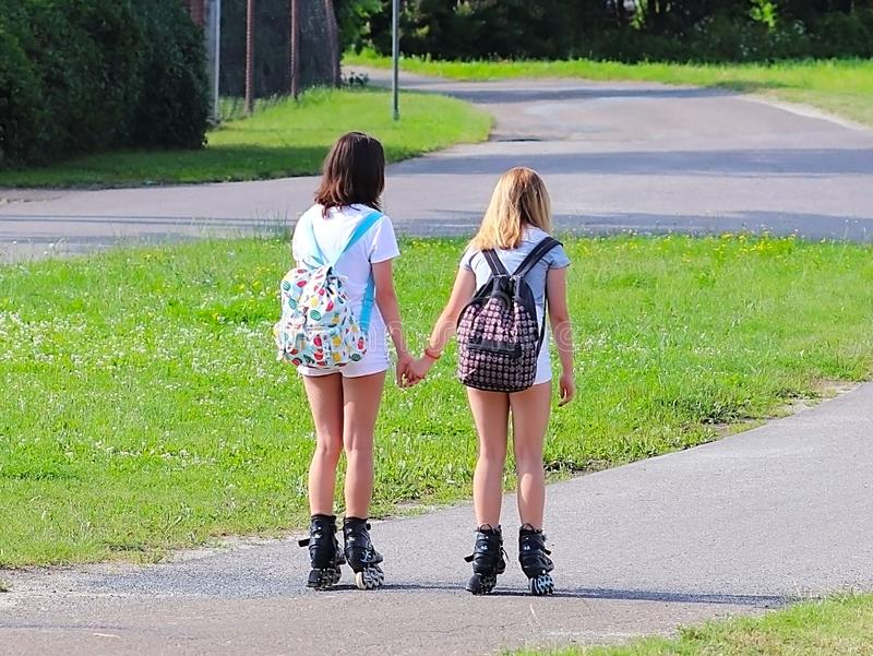Yaslo, Poland - july 10 2018: Two girls rollerblading holding hands. Active lifestyle. Children on summer vacation. Fashionable ch. Ildren`s backpacks for small stock photos