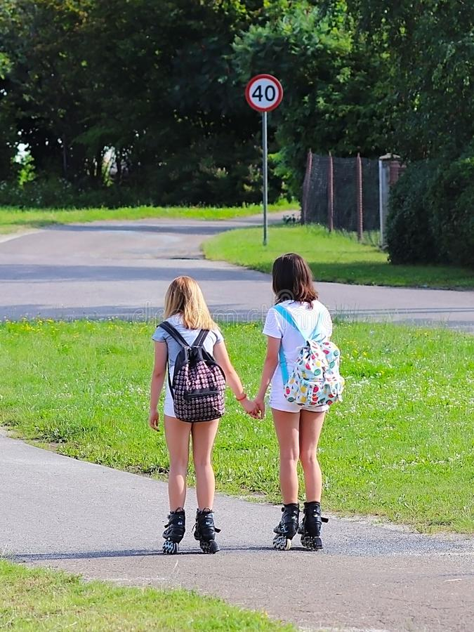Yaslo, Poland - july 10 2018: Two girls rollerblading holding hands. Active lifestyle. Children on summer vacation. Fashionable ch stock photography
