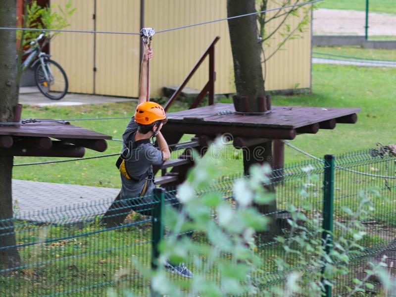 Yaslo, Poland - may 30 2018:A young paren climbs the trees in gear in a park for rock climbing. Scandinavian attraction for sports royalty free stock photo