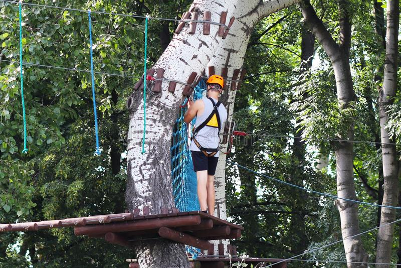 Yaslo, Poland - may 30 2018:A young paren climbs the trees in gear in a park for rock climbing. Scandinavian attraction for sports stock photography
