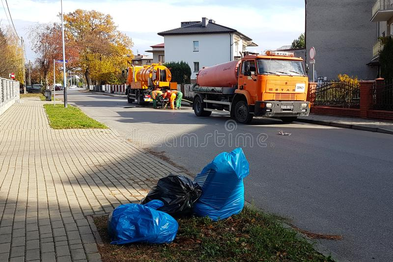 Yaslo, Poland - 9 9 2018: Sewage clearing by special technical means on the streets of a small European town. Orange cars and muni stock photography