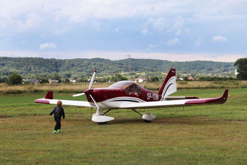 Yaslo, Pologne - 3 juillet 2018 : Le petit garçon court le long de l'aérodrome herbeux à l'avion biplace léger de tuppovintovom a images stock