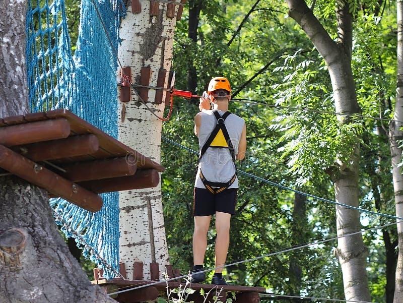 Yaslo, Polonia - puede 30 2018: Un joven paren subidas los árboles en engranaje en un parque para la escalada Atracción escandina imagen de archivo libre de regalías
