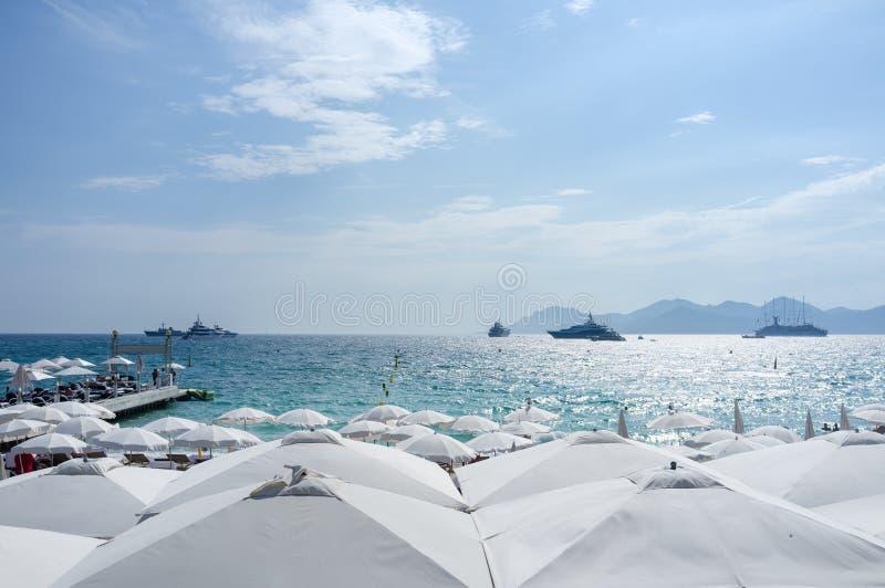 Yatchs und Regenschirme auf einem Strand in Cannes, südlich von Frankreich lizenzfreies stockbild