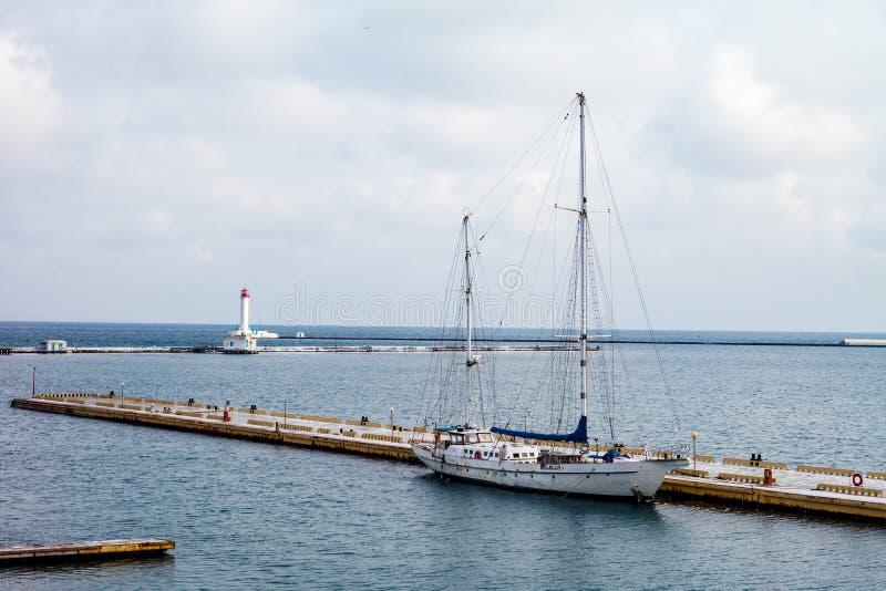 Yate blanco en el puerto y el faro fotografía de archivo