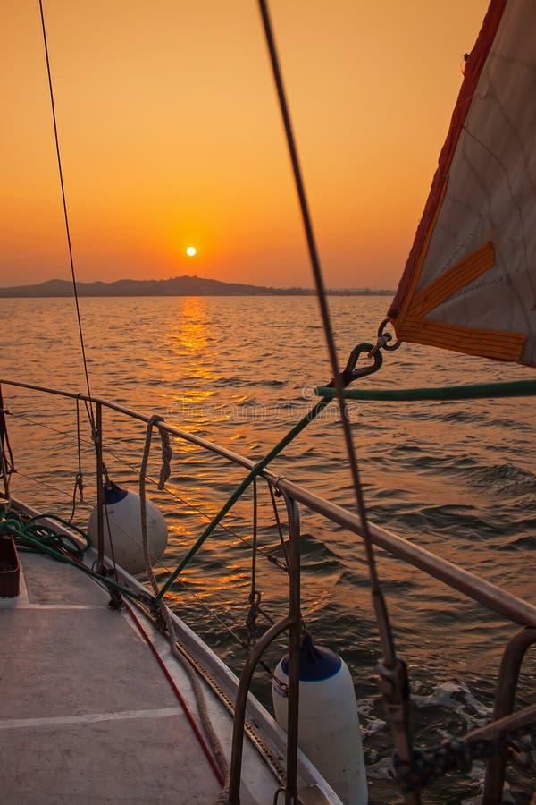 Yate de la navegación durante puesta del sol imagen de archivo