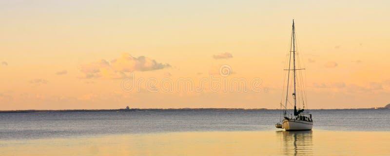 Yate de la navegación en el mar tranquilo en la puesta del sol fotografía de archivo libre de regalías