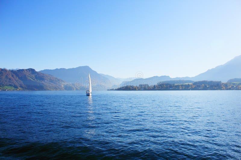 Yate debajo de la vela blanca en el lago rodeado por el canto de montañas en día soleado claro fotos de archivo libres de regalías